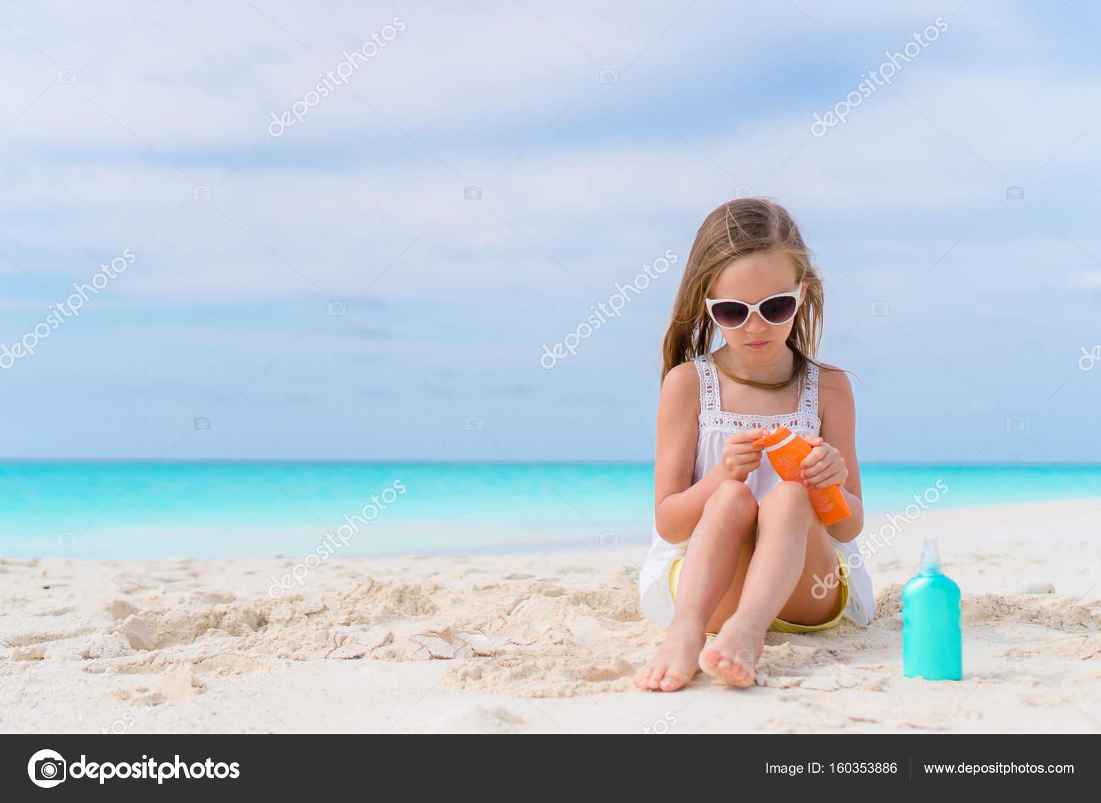Petite fille adorable, appliquer la crème pendant les vacances de plage  solaire — Image de d.travnikov ef4192874dc