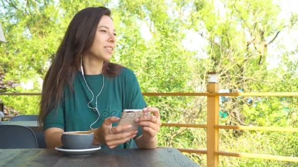 Nő a kávézóban iszik kávé mosolyogva és textil mobiltelefon okostelefon app segítségével. Szép fiatal női Profi-val mozgatható telefon.