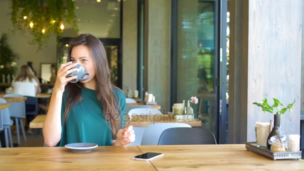 Young woman calling with cell telephone while sitting alone in coffee shop during free time. Attractive female with cute smile having talking conversation with mobile phone while rest in cafe