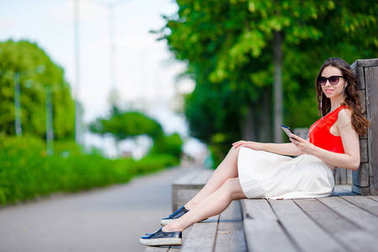 Beautiful girl listening music by smartphone on summer holidays. Young attractive tourist with mobile phone outdoors enjoying holidays.