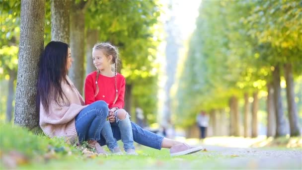 Family in fall. Young mother and little kid enjoy warm autumn