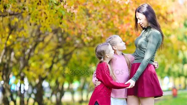 Famiglia di mamme e bambini in autunno. Giovane madre e bambine godono autunno caldo