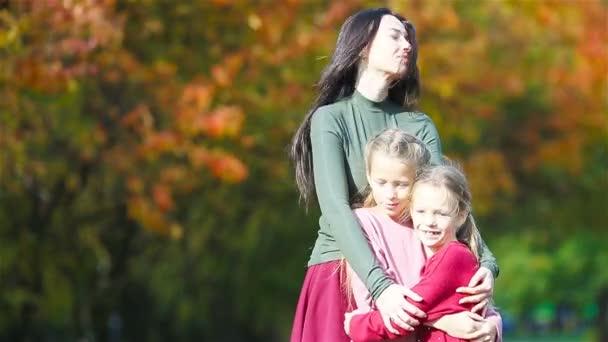 Familie mit Mutter und Kindern im Herbst. Junge Mutter und kleine Mädchen genießen warmen Herbst