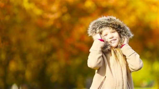 Portrait of adorable little girl with yellow trees background in fall