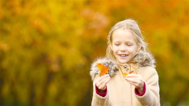 Kleine Kinder im Freien haben Spaß an einem schönen warmen Tag mit gelbem Blatt im Herbst