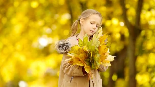 Beautiful kid with yellow and orange leaves bouquet outdoors at beautiful autumn day