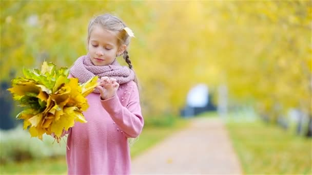 Portrait of adorable little girl with yellow and orange leaves bouquet outdoors at beautiful autumn day
