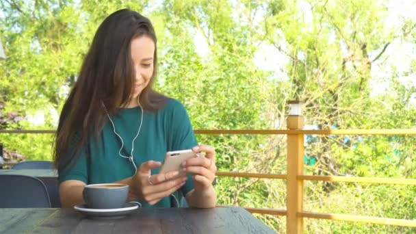 Woman using app on smartphone in cafe drinking coffee smiling and texting on mobile phone. Beautiful young female professional with mobile phone.