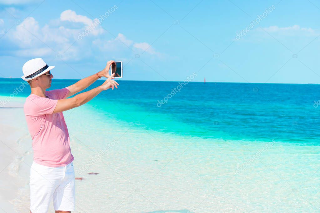 Young man with laptop on the background of turquoise ocean at tropical beach take a photo