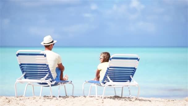 Vele fiatal apa ül a strandon a kis aranyos lány Élvezze nyaralását