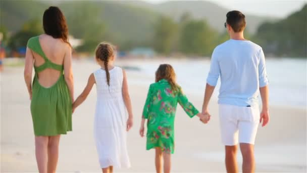 Back view of family of four with two kids walking on the beach on caribbean vacation
