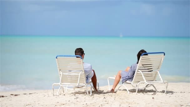 Family of two relaxing on sunbeds enjoying seaview and their holidays