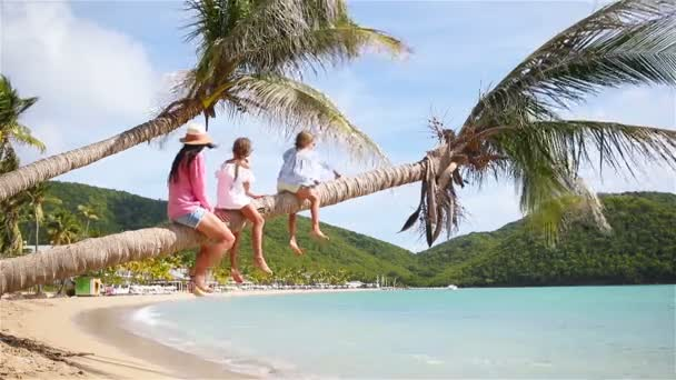 Mother and two kids having fun on white beach. Family sitting on the palm tree