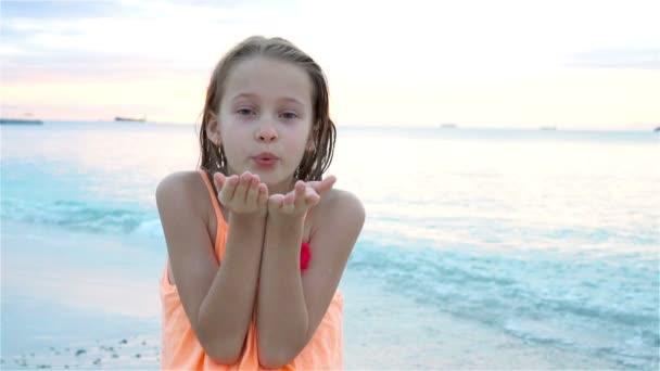 Rozkošná holčička na pláži s hodně zábavy při západu slunce. Šťastné dítě při pohledu na fotoaparát a líbání pozadí krásné nebe a moře. Zpomalený pohyb