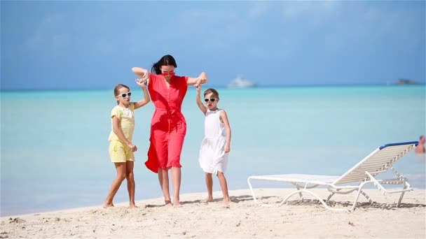 Adorable little girls and young mother having fun on white beach