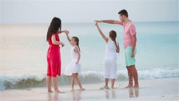 Eltern und entzückende zwei Kinder haben viel Spaß während ihres Sommerurlaubs am Strand. Vierköpfige Familie verliebt, glücklich und schön.