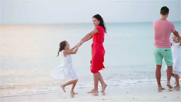 Happy beautiful family on a beach during summer vacation. Family of four have fun at sunset on the beach