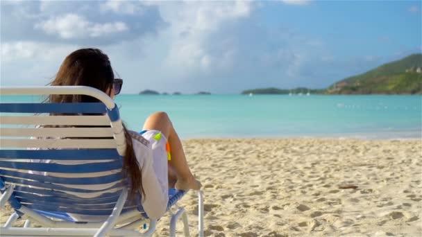 Napozzon egy napágyon fehér trópusi tengerparton nő