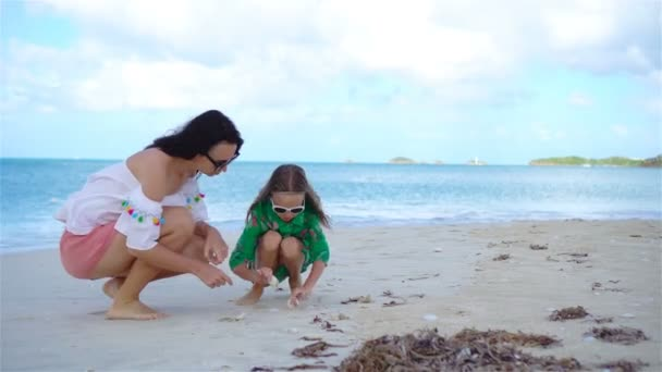 Beautiful mother and daughter on Caribbean beach looking for seashells
