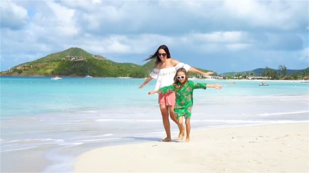 Beautiful mother and daughter on Caribbean beach. SLOW MOTION
