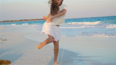 Active little girl at beach having a lot of fun. Sporty kid dancing on the seashore