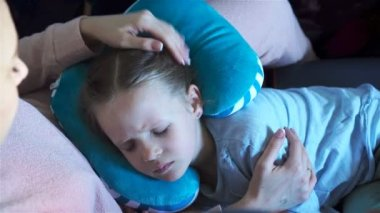 Little girl sleeping in a plane during air travel flight. Mother with daughter travel by plane