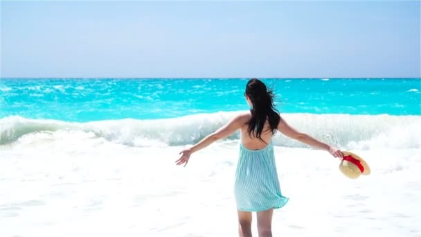 Young beautiful woman on white sand tropical beach. Back view of caucasian girl with hat background the sea