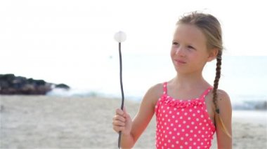 Adorable little girl at beach having a lot of fun. SLOW MOTION