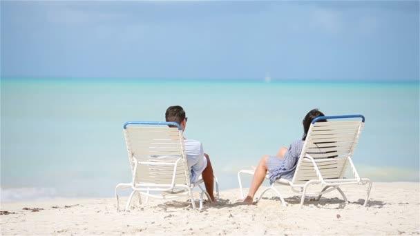 Boldog pár pihentető egy trópusi tengerparton a szolárium