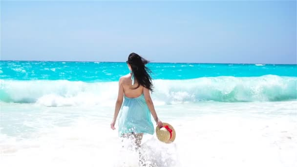 Young beautiful woman on white sand tropical beach.