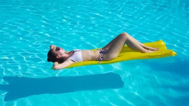 Mladá žena uvolňující na nafukovací matrace v venkovní bazén
