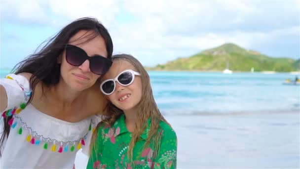 Beautiful mother and little daughter on Caribbean beach. Family taking selfie on tropical seashore