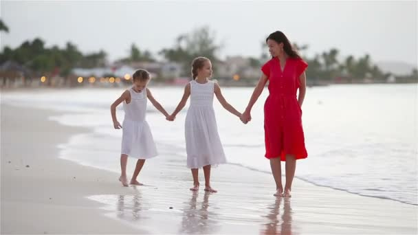 Beautiful mother and daughters on Caribbean beach. Family walking on tropical seashore