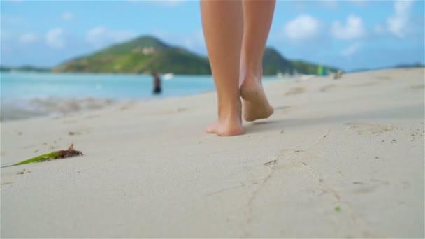 Zblízka ženské nohy, chůze naboso na pláži. Zpomalený pohyb.