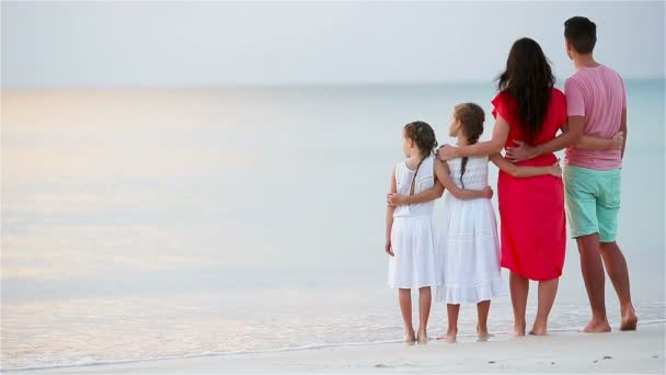 Happy beautiful family on the beach. Back view of parents and kids at sunset