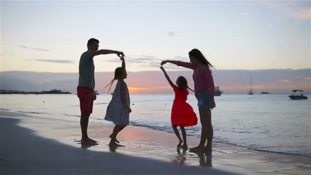 Happy beautiful family on white beach having fun in the evening
