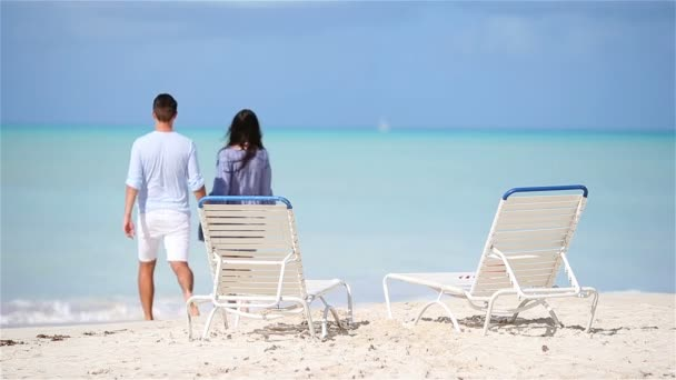 Happy couple relaxing on a tropical beach. Family of two walking together on caribbean holidays