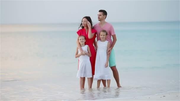 Happy family of four on white beach having fun