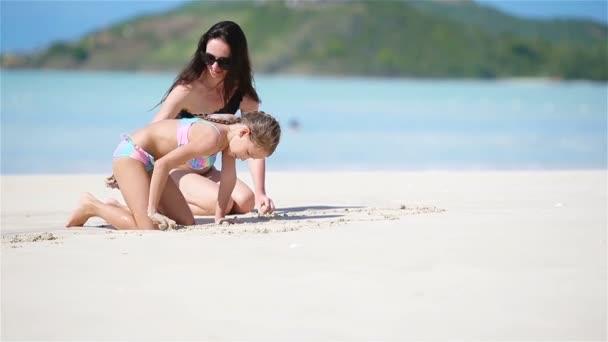 Matka a její malá dcera si pochutnávají na Karibské pláži dovolenou. Rodina hrát s pískem na tropické pláži