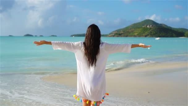 Mladá krásná žena baví na pláži th. Zadní pohled dívky na Karibské moře. Zpomalený pohyb