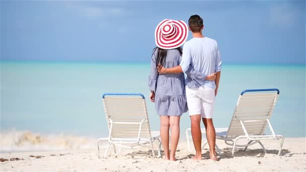 Young couple on white beach during summer vacation. Happy family enjoy their honeymoon
