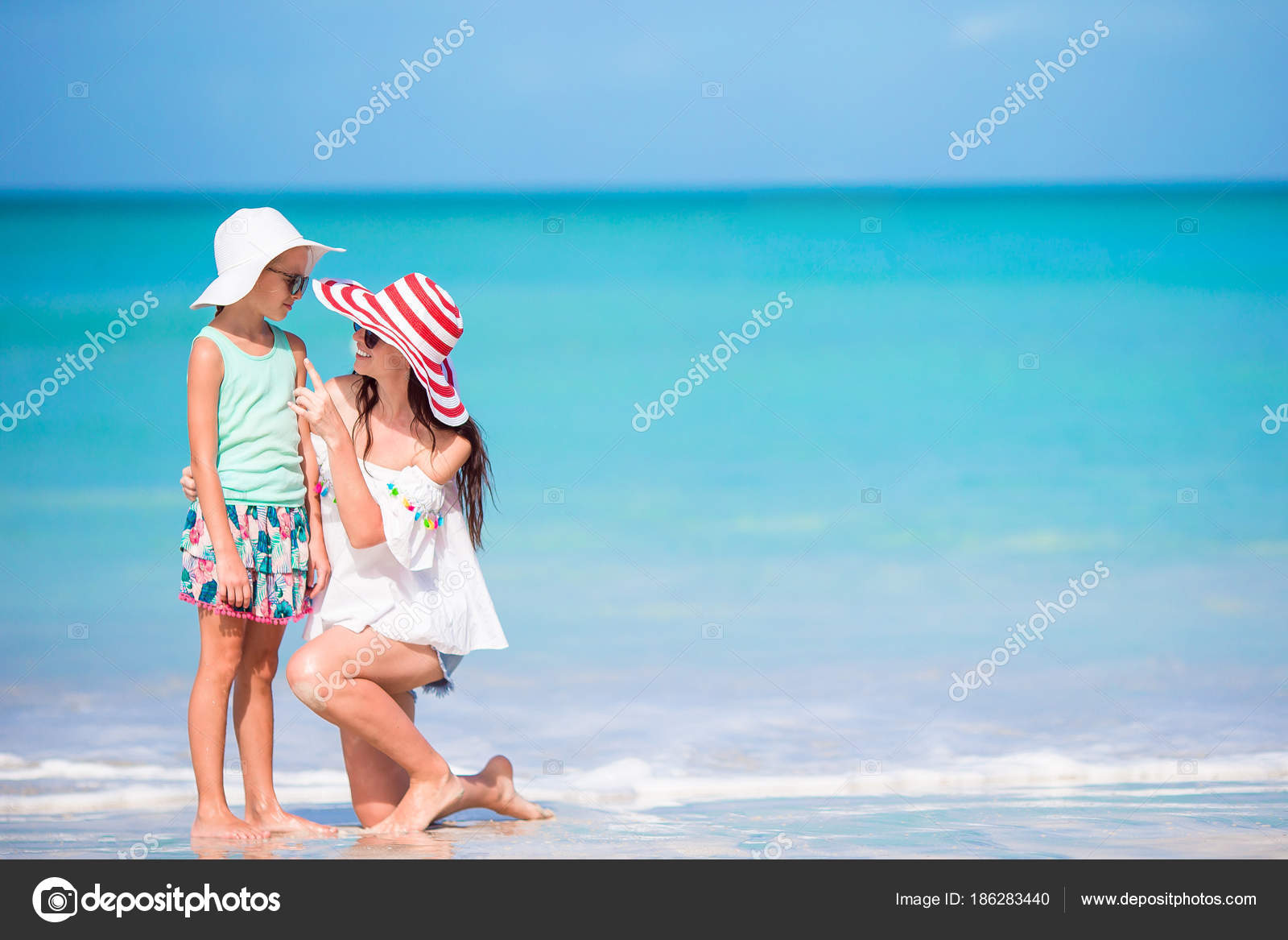 f3130f58683e5 Beautiful mother and daughter at Caribbean beach enjoying summer vacation.  Family walking on tropical famous Jolly bay beach– stock image