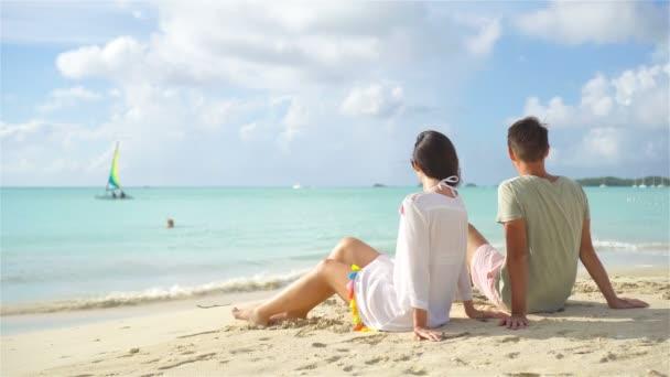 A fiatal pár, a tropical beach fehér homokos és türkizkék óceán víz a sziget Antigua Karib-térségben