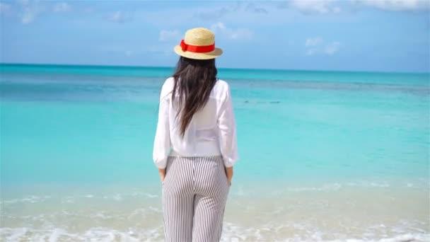 Mladá krásná žena baví na tropické pobřeží. Šťastná dívka na pozadí modré oblohy a tyrkysové vody v moři na ostrov v Karibiku.