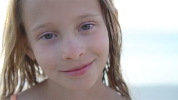 glückliches Kind blickt in die Kamera und küsst Hintergrund schönen Himmel und Meer. Zeitlupe