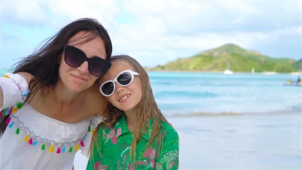 Beautiful mother and little daughter on Caribbean beach. Family taking selfie on tropical seashore. SLOW MOTION