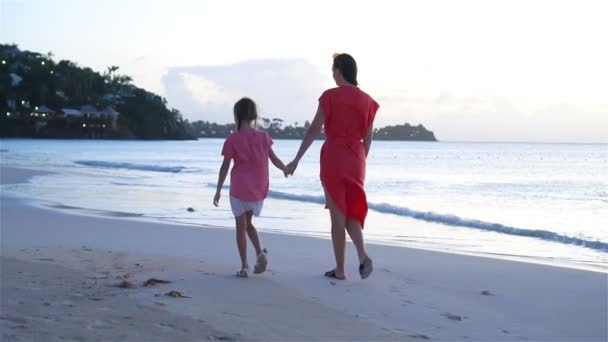 Beautiful mother and daughter on Caribbean beach. Family on beach vacation. SLOW MOTION