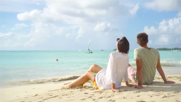 Young couple on tropical beach with white sand and turquoise ocean water at Antigua island in Caribbean
