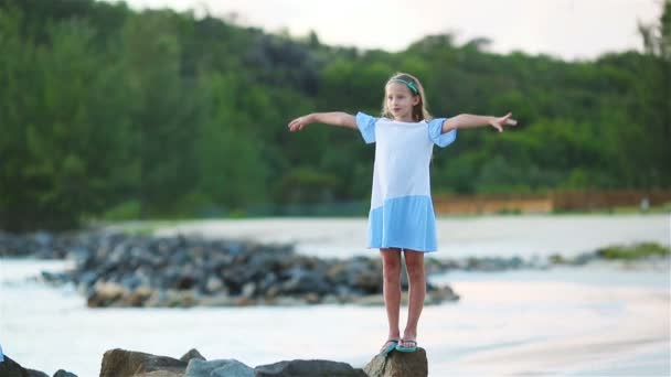 Adorable little girl on wild exotic beach at tropical caribbean island
