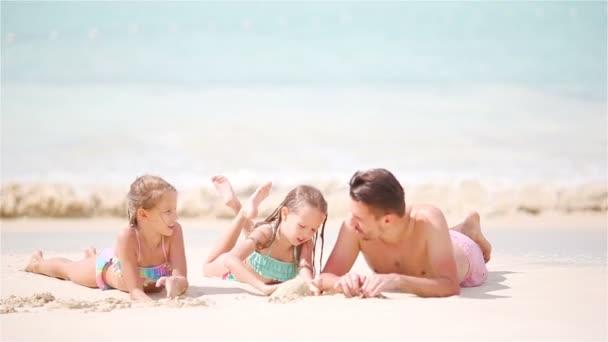 Rodina baví na bílé pláži. Děti a táta ležel v mělké vodě